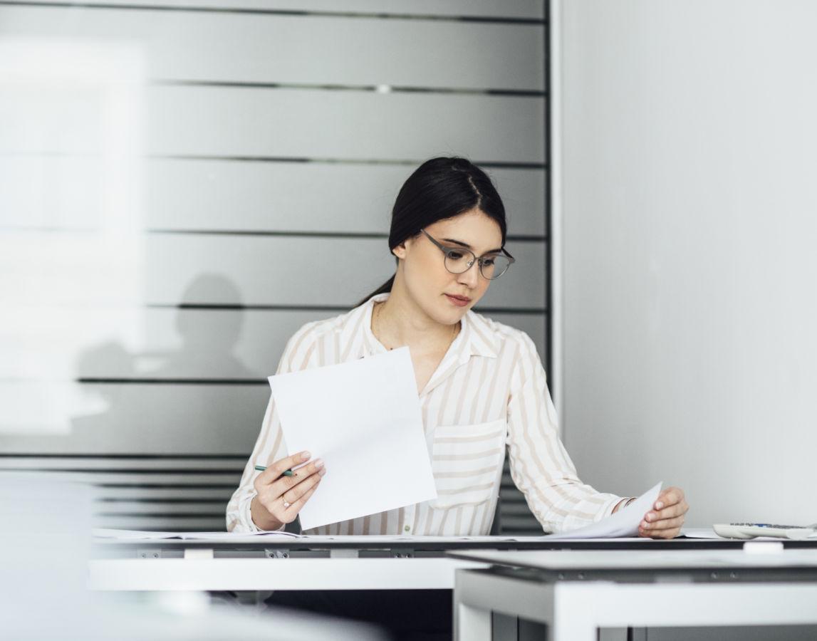 Pretty elegant Caucasian woman teacher grading exam papers at school.