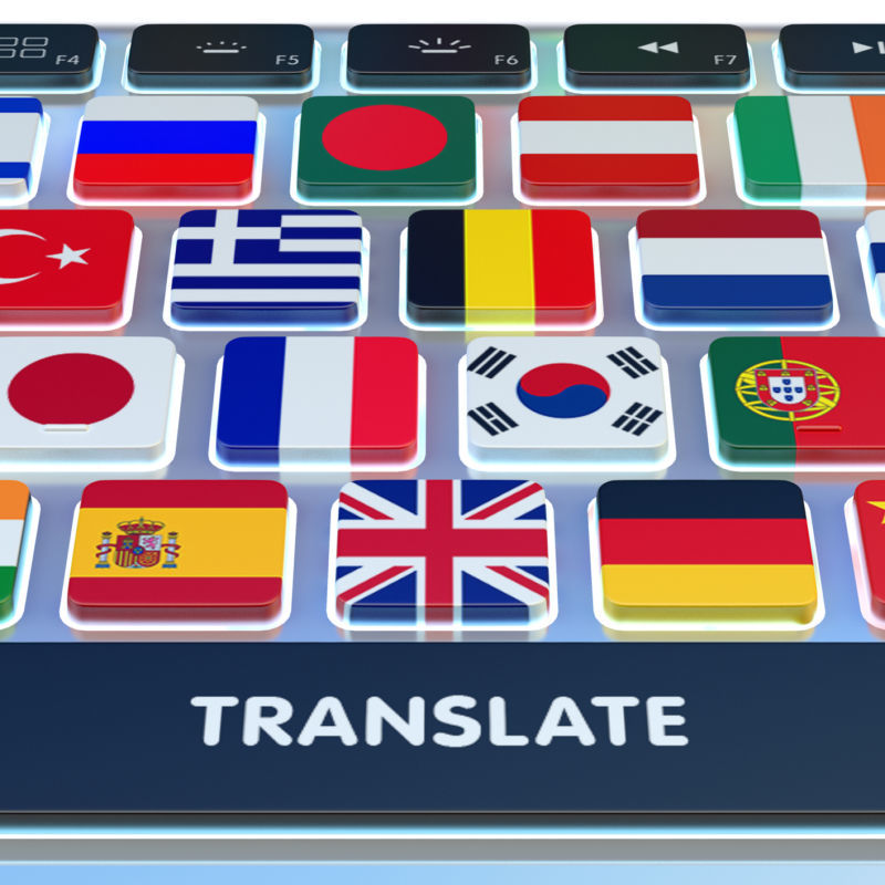Close-up view of computer keyboard with national flags of world countries on keys and translate button