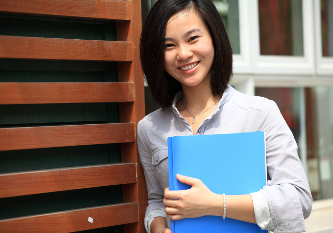 """""""The young Asian business woman smiling outdoors, holding a folder"""""""