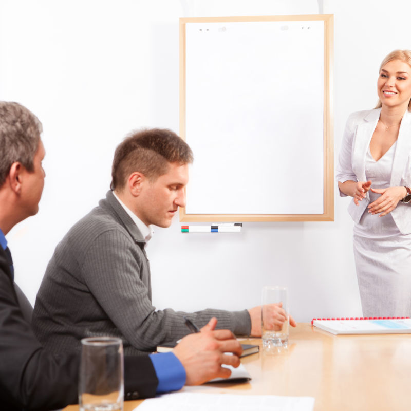 Young Businesswoman Presenting His Ideas on Flip Chart to Colleagues